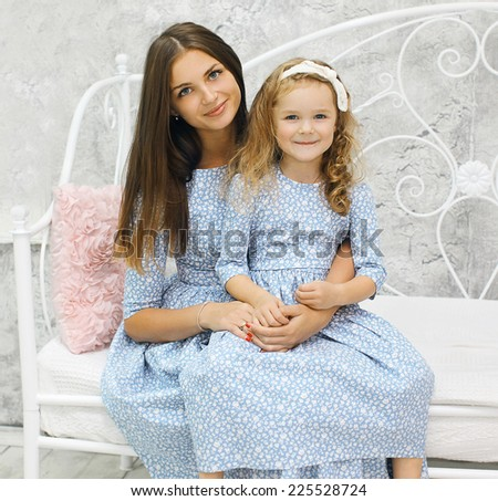 Beauty mother and daughter in dress sitting on the bed home - stock photo