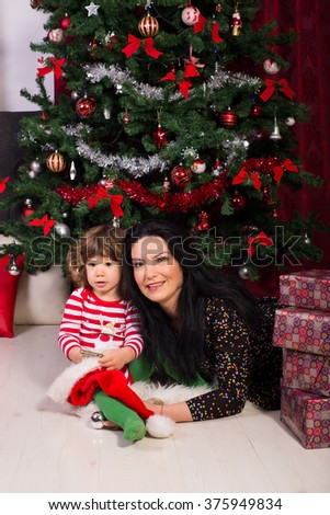 Beauty mother and son laying in front of Christmas tree with presents - stock photo