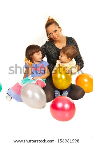 Beauty mother holding two kids at party with balloons - stock photo