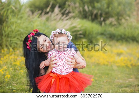 Beauty Mum and her Child playing in Park together. Outdoor