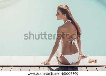 Beauty near the pool. Rear view of attractive young woman in white bikini sitting by the pool and looking away - stock photo