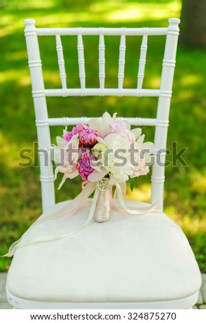 Beauty of colored flowers. Bridal accessories. Close-up bunch of florets. Details for marriage and for married couple. Wedding bouquet with peonies, roses and orchids on the white chair