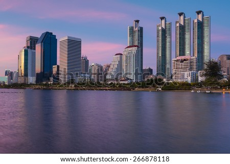 Beauty of twiligh time, Bangkok business building in public park with water reflection - stock photo