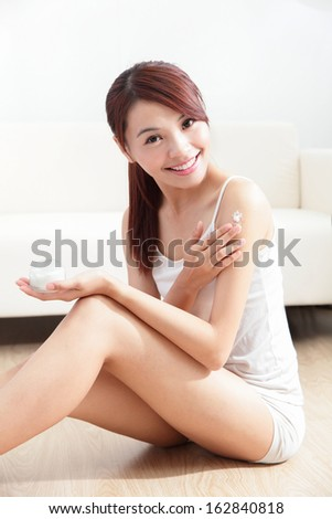 Beauty of young woman applying cream on her skin indoors at home, asian beauty