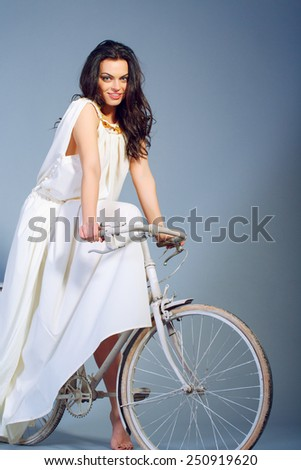 Beauty on bicycle. Conceptual photo of free beauty in white long dress riding a bicycle and smiling to camera while standing against grey background with copy space - stock photo