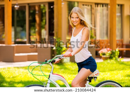 Beauty on bicycle. Side view of beautiful young blond hair woman smiling and looking at you while riding her bicycle outdoors  - stock photo
