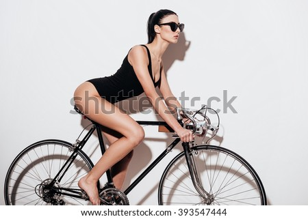 Beauty on bicycle. Side view of beautiful young woman in black swimsuit sitting on the bicycle against white background - stock photo