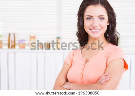 Beauty on the kitchen. Beautiful young woman keeping arms crossed and smiling while standing in a kitchen - stock photo