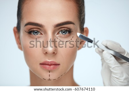 Beauty Operation. Closeup Of Beautician Hand With Scalpel Near Young Woman Face. Portrait Of Beautiful Woman With Perfect Makeup And Surgical Lines On Soft Skin. Facial Treatment. High Resolution