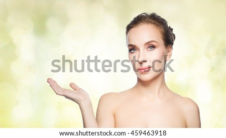 beauty, people, advertisement and health concept - smiling young woman holding something on palm of her hand over yellow holidays lights background