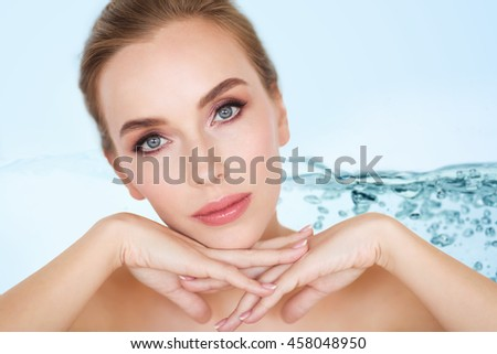 beauty, people and body care concept -beautiful young woman face and hands over water splash bubbles on blue background - stock photo