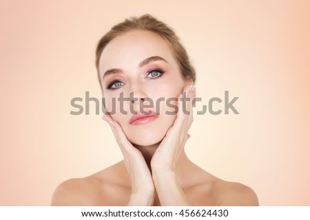 beauty, people and bodycare concept -beautiful young woman face and hands over beige background - stock photo