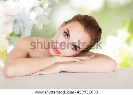 beauty, people and bodycare concept -beautiful young woman face and hands over natural spring cherry blossom background - stock photo