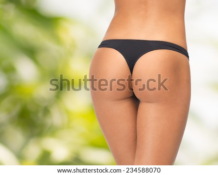 beauty, people and bodycare concept - close up of female legs in black bikini panties over green background