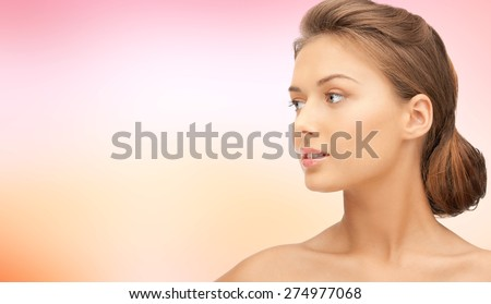beauty, people and health concept - beautiful young woman face looking aside over pink background - stock photo