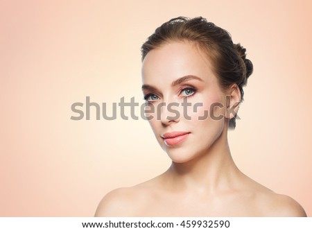 beauty, people and health concept - beautiful young woman face over beige background - stock photo