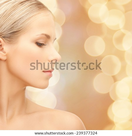beauty, people and health concept - beautiful young woman face over beige lights background