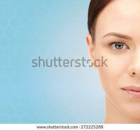 beauty, people and health concept - beautiful young woman face over blue background - stock photo