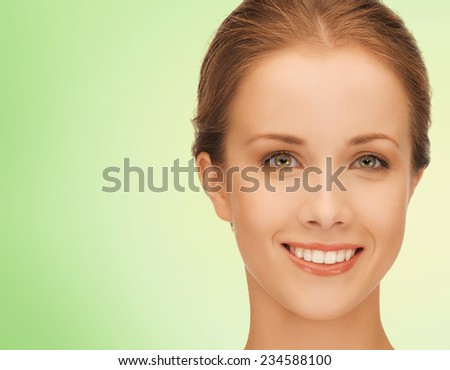 beauty, people and health concept - beautiful young woman face over green background - stock photo