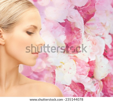 beauty, people and health concept - beautiful young woman face over pink floral background - stock photo