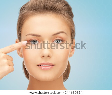 beauty, people and health concept - beautiful young woman pointing finger to her eye over blue background - stock photo