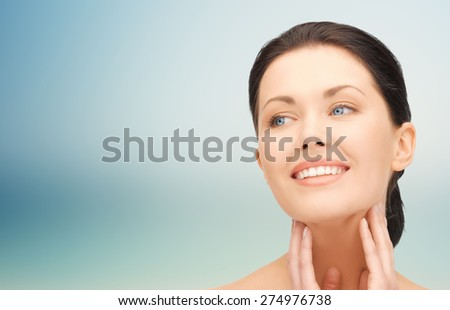 beauty, people and health concept - beautiful young woman touching her face and neck over blue background - stock photo