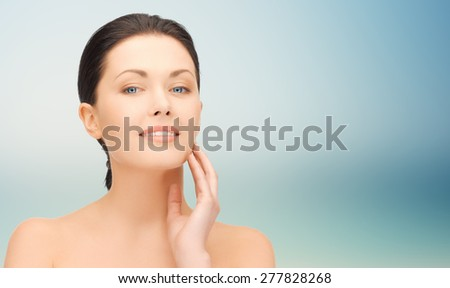 beauty, people and health concept - beautiful young woman touching her face over blue background - stock photo