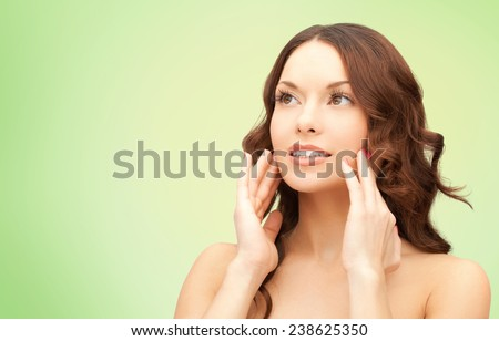 beauty, people and health concept - beautiful young woman touching her face over green background - stock photo