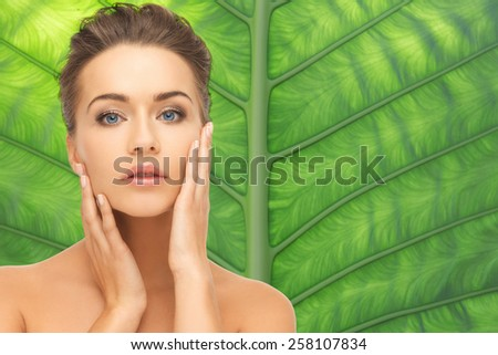 beauty, people and health concept - beautiful young woman touching her face over green palm leaf background - stock photo