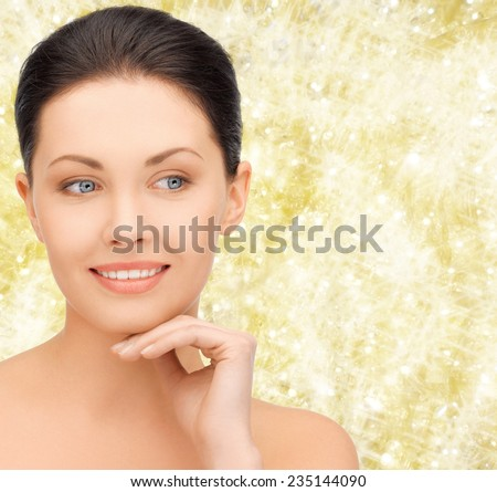 beauty, people and health concept - beautiful young woman touching her face over yellow lights background