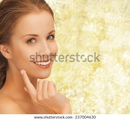beauty, people and health concept - beautiful young woman touching her face over yellow lights background - stock photo