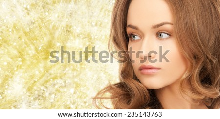 beauty, people and health concept - beautiful young woman with bare shoulders over yellow lights background