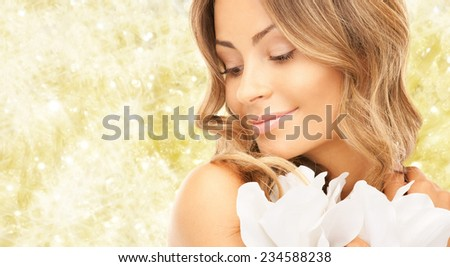 beauty, people and health concept - beautiful young woman with flowers and bare shoulders over yellow lights background