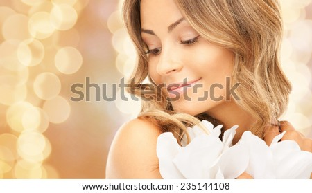 beauty, people and health concept - beautiful young woman with flowers and bare shoulders over beige lights background