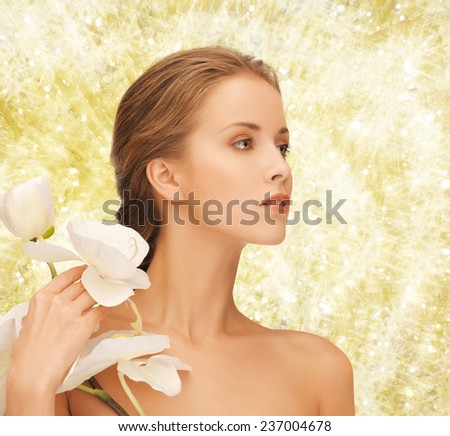 beauty, people and health concept - beautiful young woman with orchid flowers and bare shoulders over yellow lights background - stock photo