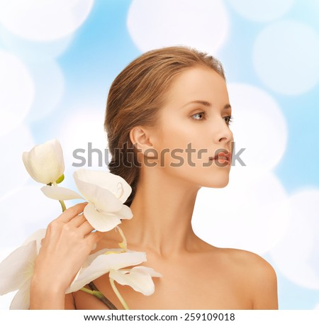 beauty, people and health concept - beautiful young woman with orchid flowers and bare shoulders over blue lights background - stock photo