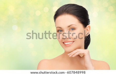 beauty, people and health concept - close up of beautiful young woman face over green lights background