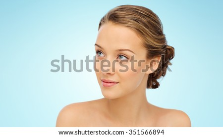 beauty, people and health concept - smiling young woman face and shoulders over blue background - stock photo