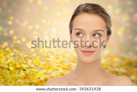beauty, people and health concept - smiling young woman face and shoulders over golden glitter or holidays lights background - stock photo