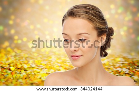 beauty, people and health concept - smiling young woman face and shoulders over golden holidays lights or yellow glitter background - stock photo