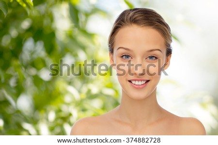 beauty, people and health concept - smiling young woman face and shoulders over green natural background - stock photo