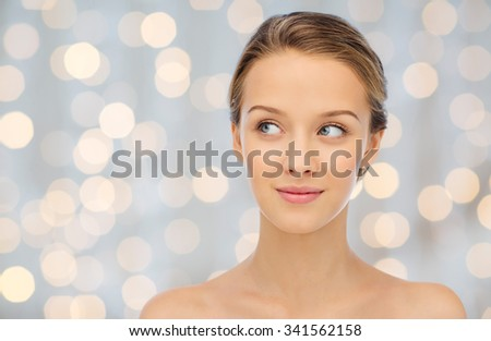 beauty, people and health concept - smiling young woman face and shoulders over holidays lights background - stock photo