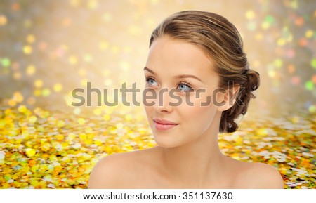 beauty, people and health concept - smiling young woman face and shoulders over yellow glitter and confetti background - stock photo