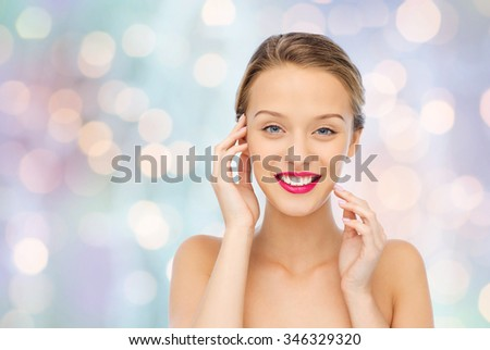 beauty, people and health concept - smiling young woman face with pink lipstick on lips and shoulders over blue holidays lights background - stock photo