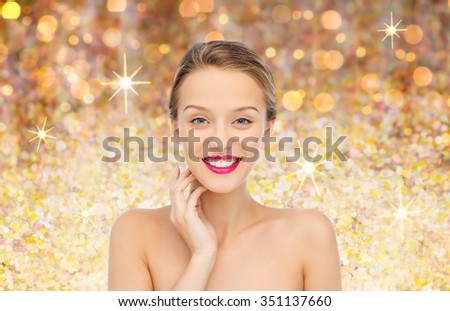 beauty, people and health concept - smiling young woman face with pink lipstick on lips and shoulders over golden glitter background - stock photo