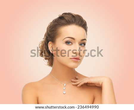 beauty, people and jewelry concept - woman wearing shiny diamond pendant over pink background - stock photo