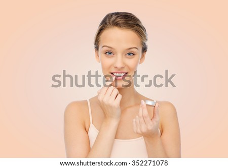 beauty, people and lip care concept - smiling young woman applying lip balm to her lips over beige background - stock photo