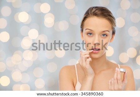 beauty, people and lip care concept - young woman applying lip balm to her lips over holidays lights background - stock photo