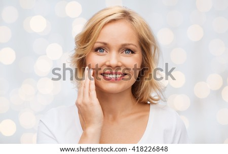 beauty, people and skincare concept - smiling woman in white shirt touching face over holidays lights background - stock photo