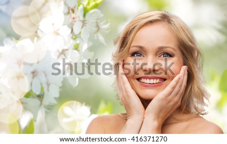 beauty, people and skincare concept - smiling woman with bare shoulders touching face over natural spring cherry blossom background - stock photo